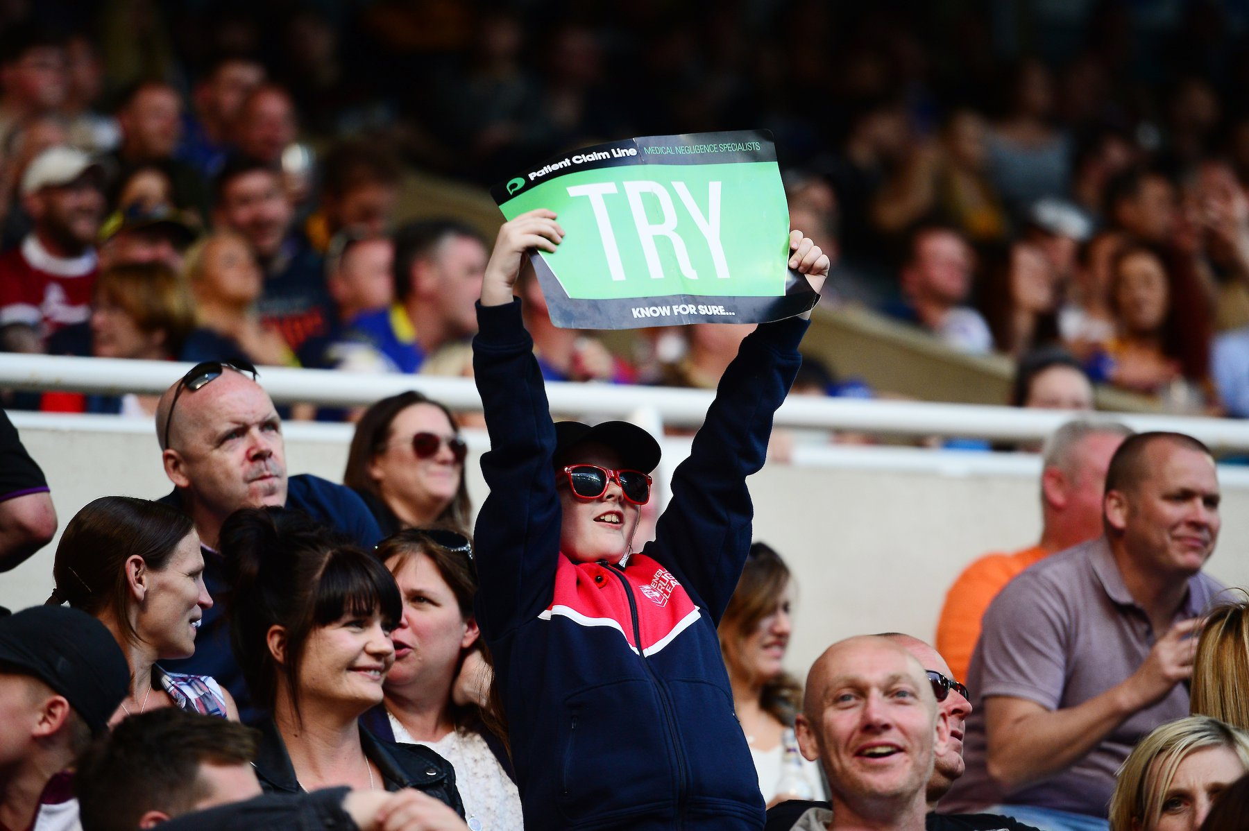 Boy holding Patient Claim Line sign at Betfred Rugby Super League game